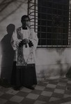 Fr. Paul Yu Bin standing next to a Chinese stone lion