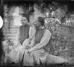 Fr. Vincent Lebbe and Fr. Anthony Cotta, MM, Seated Outside a Building